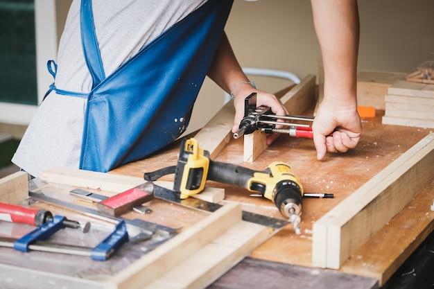 Holzbearbeiter verwenden holzbearbeitungswerkzeuge, um einen bohrer vorzubereiten, bohren löcher in holz, um einen holztisch für ihre kunden zusammenzubauen und zu bauen