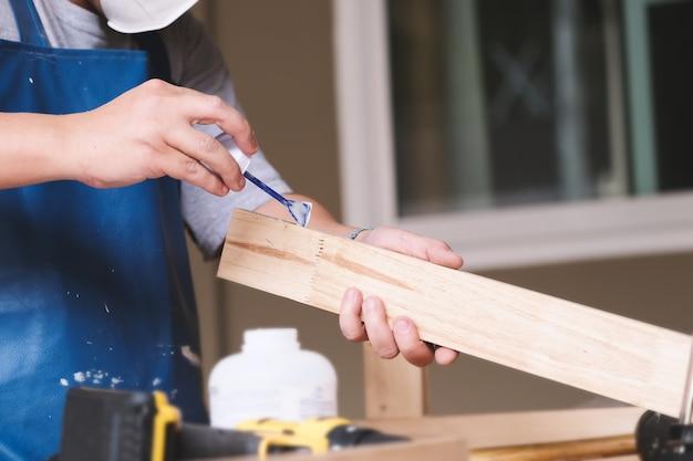 Holzbearbeiter verwenden klebstoff, um die holzteile zusammenzusetzen und einen holztisch für ihre kunden zu montieren und zu bauen