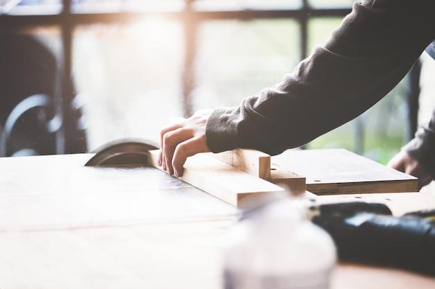 Holzbearbeiter verwenden sägeblätter, um holzstücke zu schneiden und holztische für ihre kunden zusammenzubauen und zu bauen.