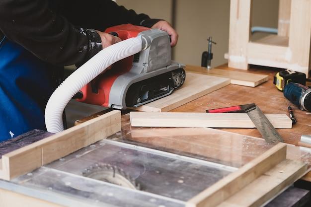 Holzbearbeiter verwenden sandpapierveredelungsmaschinen, um holztische für ihre kunden zu montieren und zu bauen