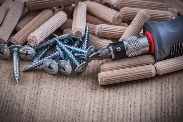 Holzbearbeitungsdübel metallkonstruktionsnägel isolierter schraubendreher auf holzplatte