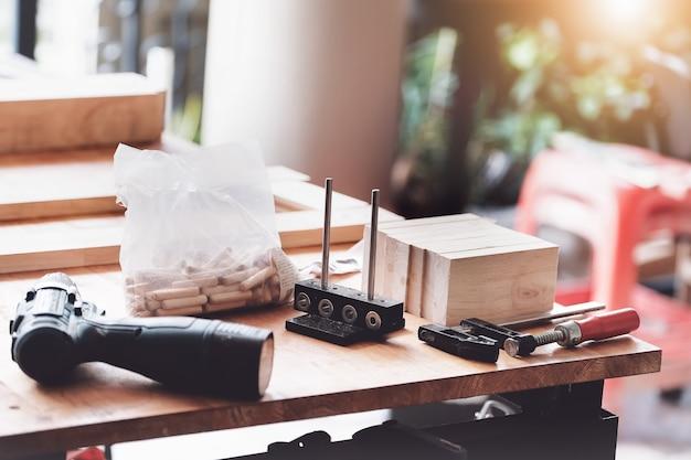 Holzbearbeitungsgeräte wie sperrholz, bohrer, arbeitswerkzeug, messschieber auf dem arbeitstisch