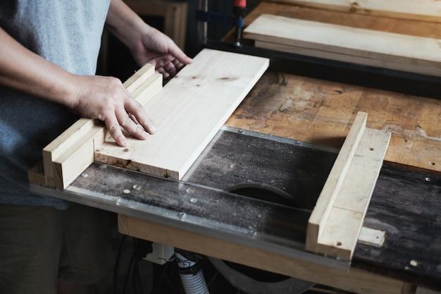 Holzbearbeitungspraktiker verwenden sägeblätter, um holzstücke zu schneiden, um holztische zu montieren und zu bauen