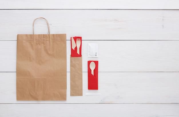 Holzbesteck und papiertüte auf holztisch. kein plastikkonzept