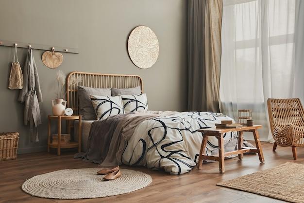 Holzbett in stilvollem, neutralem schlafzimmer mit designmöbeln, dekoration, teppich, bank, getrockneten blumen in der vase, bettwäsche, decke, kissen und eleganten persönlichen accessoires in wohnkultur.