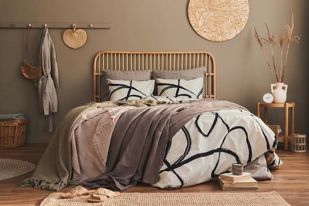 Holzbett in stilvollem, neutralem schlafzimmer mit designmöbeln, dekoration, teppich, buch, getrockneten blumen in der vase, bettwäsche, decke, kissen und eleganten persönlichen accessoires in wohnkultur.