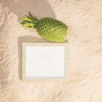 Holzbilderrahmen und ananas auf sand