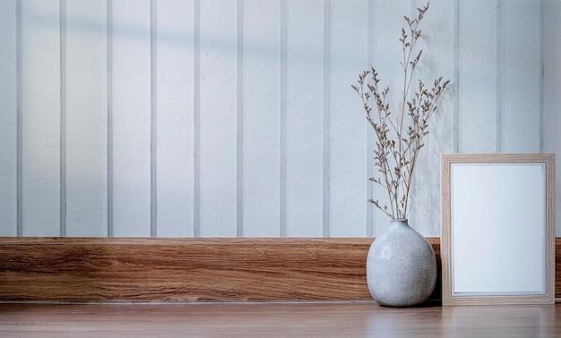 Holzbilderrahmen und keramikvase mit blume auf holztisch, kopienraum.
