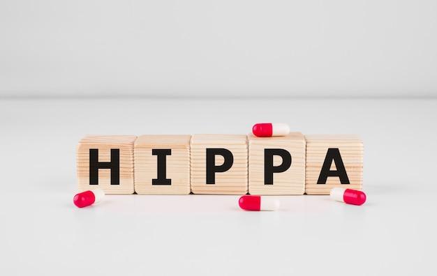 Holzblock bilden das wort hipaa health insurance portability and accountability act auf weiß. medizinisches konzept.