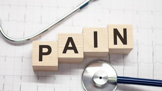 Holzblock bilden das wort schmerz mit stethoskop auf dem desktop des arztes. medizinisches konzept. gesundheitskonzept für krankenhaus, klinik und medizinisches geschäft medical