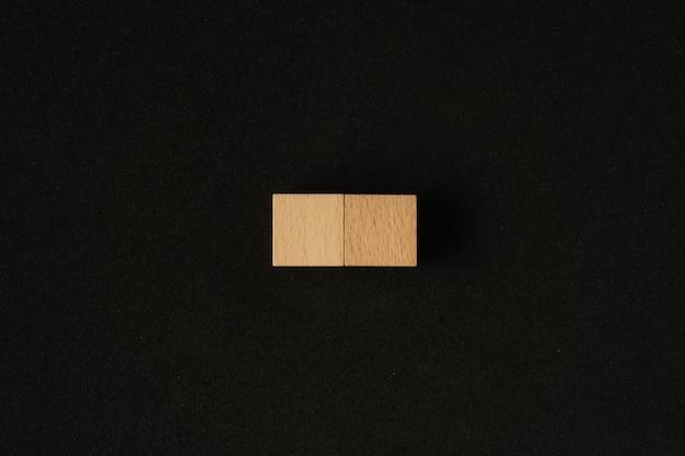 Holzblock mit kopienraum auf schwarzem hintergrund.