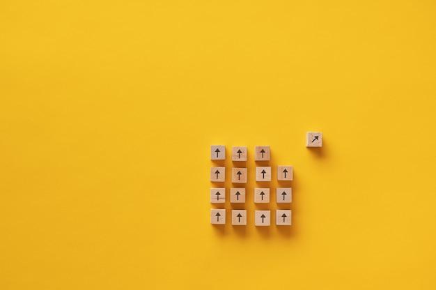 Holzblock mit pfeil darauf, der sich von einer gruppe anderer blöcke in einem konzeptuellen bild von vision und entschlossenheit trennt.