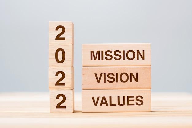 Holzblock mit text 2022 mission, vision und value auf tabellenhintergrund. vorsatz, strategie, lösung, ziel, geschäfts- und neujahrsferienkonzepte