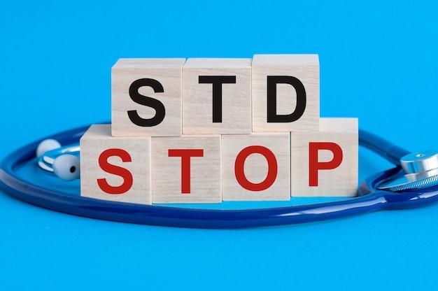 Holzblock mit worten stop std - sexuell übertragbare krankheiten - mit stethoskop auf dem tisch, gesundheitskonzept, blau
