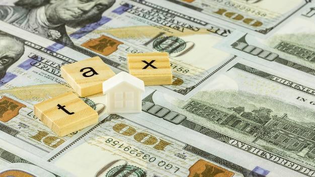 Holzblock und ein kleines hauptmodell auf dollarscheinen. steuerkonzept.