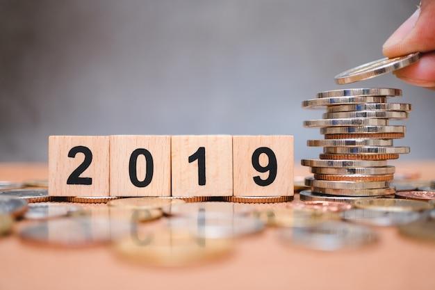 Holzblockjahr 2019 mit der hand, die stapelmünzen unter verwendung als geschäfts- und finanzkonzept hält