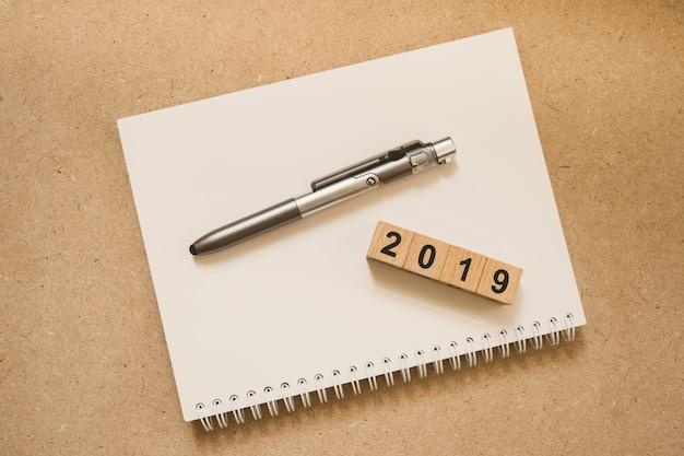 Holzblockjahr 2019 und stift auf weißem notizbuch
