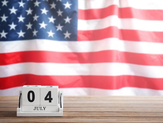 Holzblockkalender gegenwärtiges datum 04. juli auf braunem holztisch über usa-flaggenunschärfehintergrund