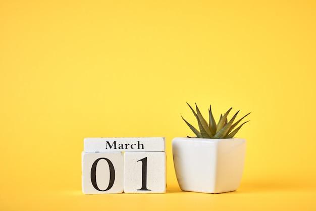 Holzblockkalender mit datum 1. märz und pflanze auf gelb. frühlingskonzept