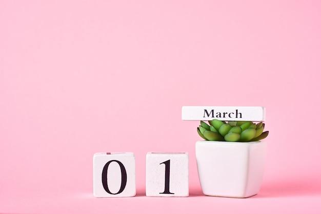 Holzblockkalender mit datum 1. märz und pflanze auf rosa. frühlingskonzept