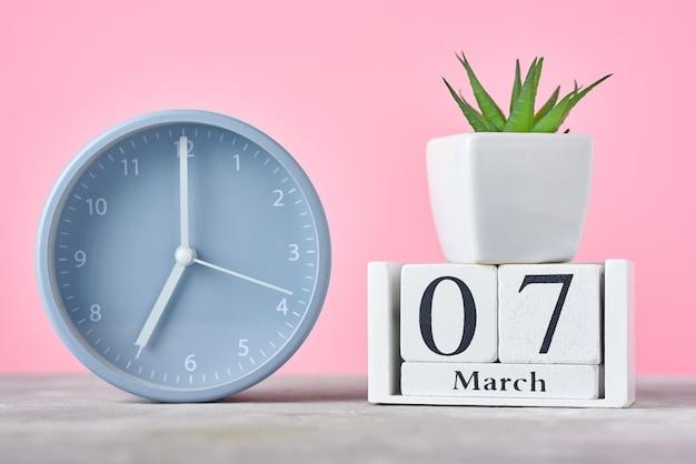 Holzblockkalender mit datum 7. märz, wecker und pflanze auf rosa