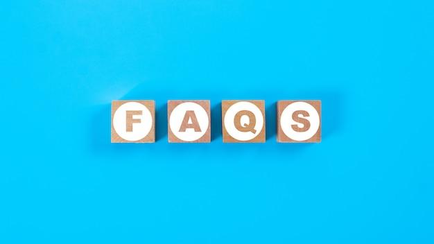 Holzblockwürfel für faqs formulierung auf blauem hintergrund