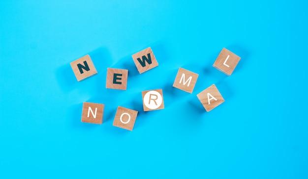 Holzblockwürfel für neuen normalen wortlaut. die welt verändert sich, um sie in eine neue normalität zu bringen, darunter wirtschaft, wirtschaft, umwelt und gesundheit.