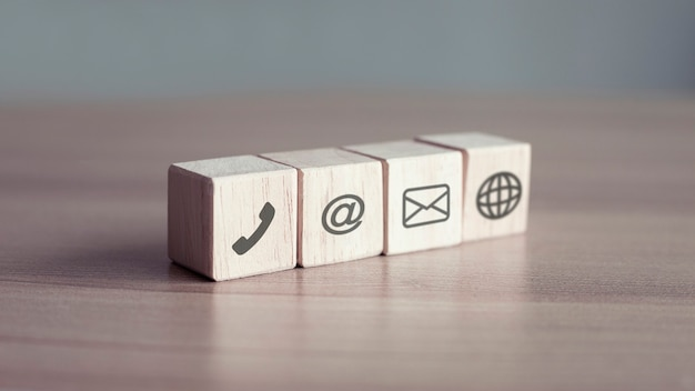 Holzblockwürfelsymbol telefonadresse mail social auf holztisch
