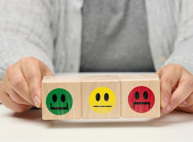 Holzblöcke mit verschiedenen emotionen von lächeln bis traurigkeit und die hand einer frau. konzept zur beurteilung der qualität eines produkts oder einer dienstleistung, emotionaler zustand, nutzerbewertungen