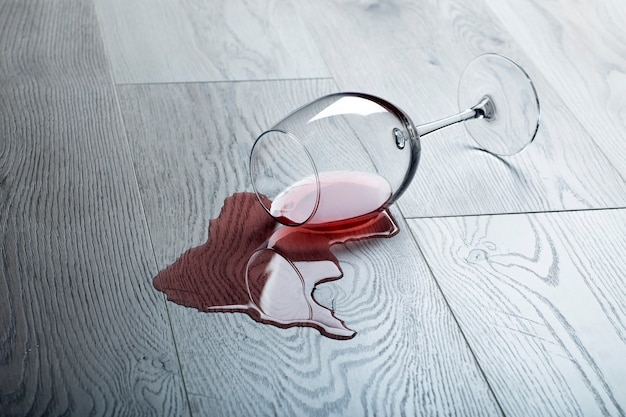 Holzboden mit umgekipptem glas rotwein. verschütteter wein auf einem holzlaminatboden (parkett) mit feuchtigkeitsschutz.