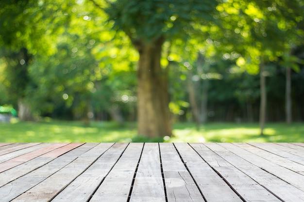 Holzboden mit verschwommenen bäumen des naturparkhintergrundes