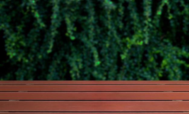 Holzboden und verschwommene grüne pflanzenwand