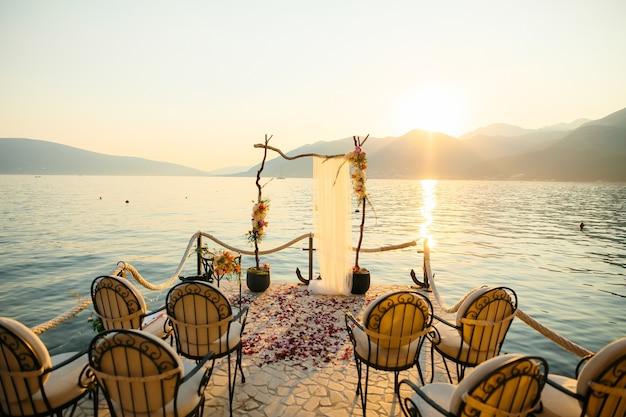 Holzbogen für die hochzeitszeremonie bei sonnenuntergang