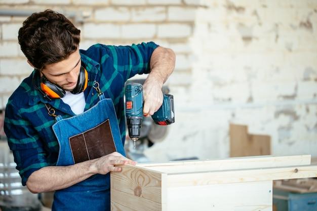 Holzbohrer in handbohrloch in holzstange