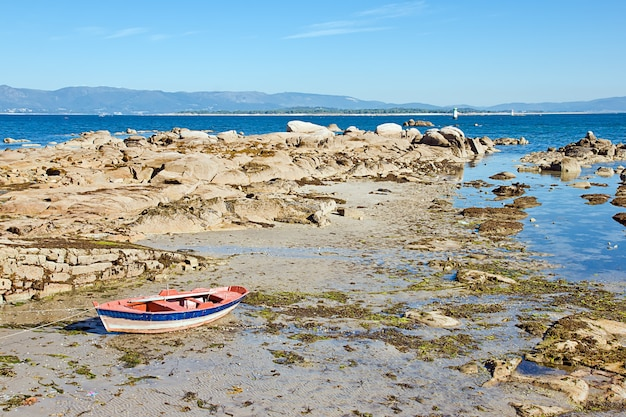 Holzboot am sand- und felsstrand unter blauem himmel the