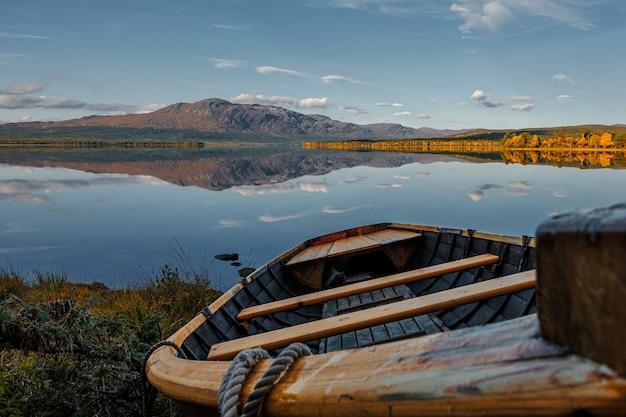 Holzboot am ufer eines großen schönen ruhigen sees