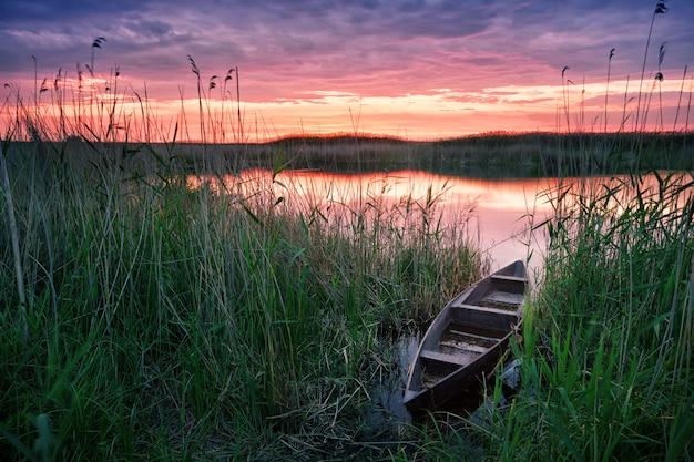 Holzboot auf dem see bei sonnenuntergang