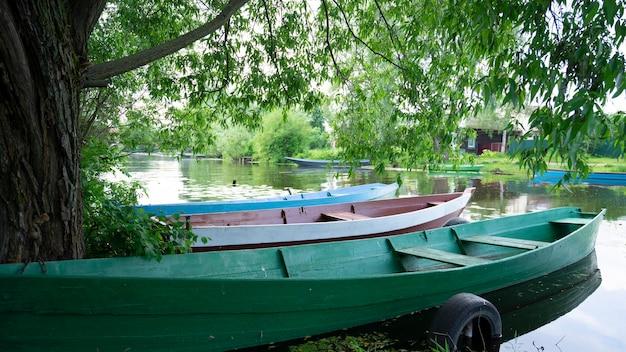 Holzboote auf dem fluss zwischen den bäumen. pereslavl-zalessky, goldener ring russlands.