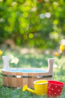 Holzbottich, gießkanne und eimer auf grünem gras im frühlingsgarten