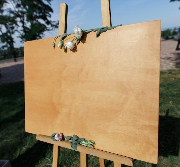 Holzbrett auf staffelei zum schreiben oder zum zeichnen mit textfreiraum. stilvolle festliche einrichtung auf der hochzeitsfeier.