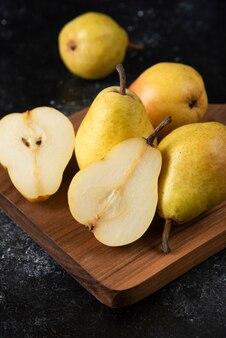 Holzbrett aus köstlichen gelben birnen auf schwarzer oberfläche.