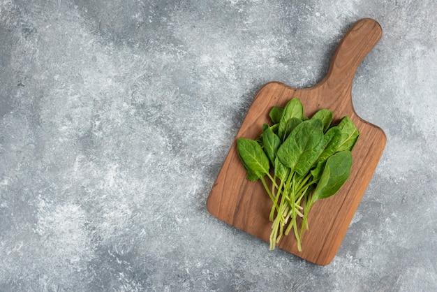 Holzbrett der frischen gesunden grünen blätter auf marmor.