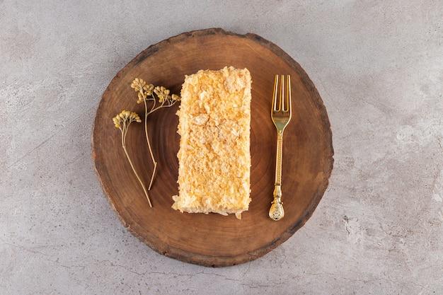 Holzbrett des hausgemachten honigkuchens auf steinoberfläche