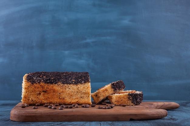 Holzbrett des köstlichen biskuitkuchens auf marmorhintergrund.