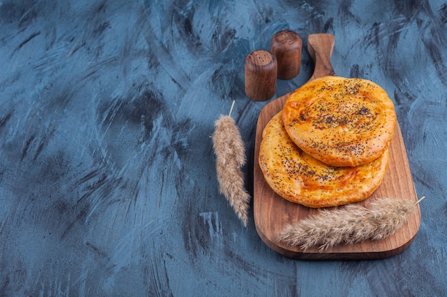 Holzbrett des köstlichen duftenden gebäcks auf marmorhintergrund.