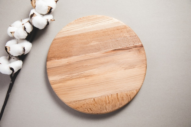 Holzbrett mit baumwollzweig auf der grauen oberfläche