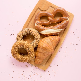 Holzbrett mit brezel und croissant