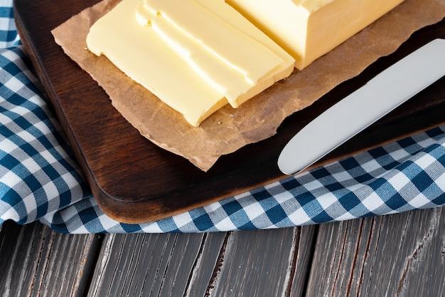 Holzbrett mit butter auf blau karierter serviette