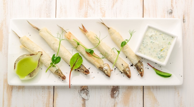 Holzbrett mit geschmolzenem gebratenem fisch und salat