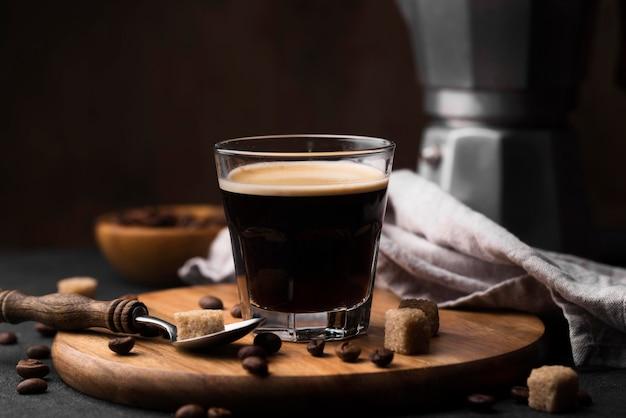 Holzbrett mit glas kaffee auf dem tisch
